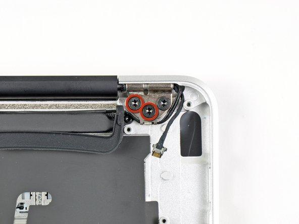 Entferne die inneren zwei 4,9 mm T8 Torx Schrauben, mit denen der Antennenkabelhalter und das linke Verschlussscharnier am oberen Gehäuse festgemacht ist.