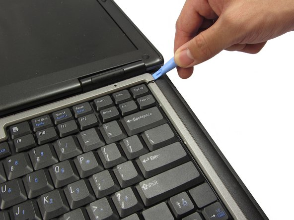 Using a plastic opening tool, pry off the corner of the keyboard bezel by undoing the tab.