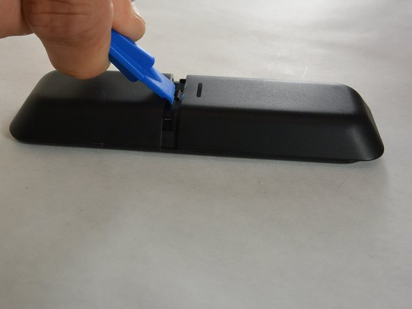 Use a plastic opening  tool to open the battery cover.  Apply a small amount of force into the crease.