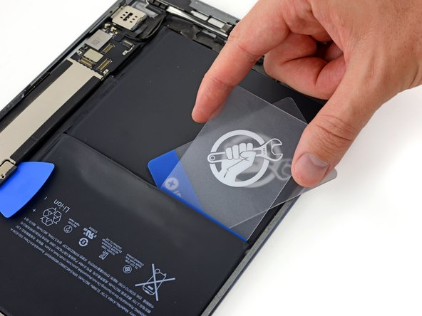 Slide the short edge of a second plastic card underneath the battery cell and above the first plastic card.