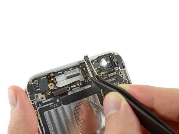 Use a pair of tweezers to firmly grasp the plastic clip and remove it from the iPhone.