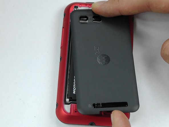 Remove the back cover of the phone by sliding the bottom black button to the unlock position and lifting it up.
