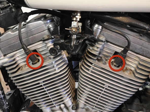 The spark plugs are easy to spot on the left side of the motorcycle.