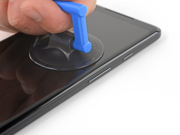 Pull up on the suction cup with firm, constant pressure and insert an opening pick between the front panel and rear case.
