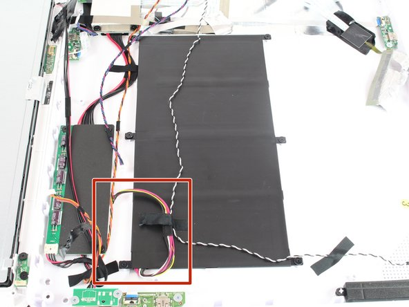 Locate the bundle of wires connecting the battery to the power regulator, which is right next to the battery.