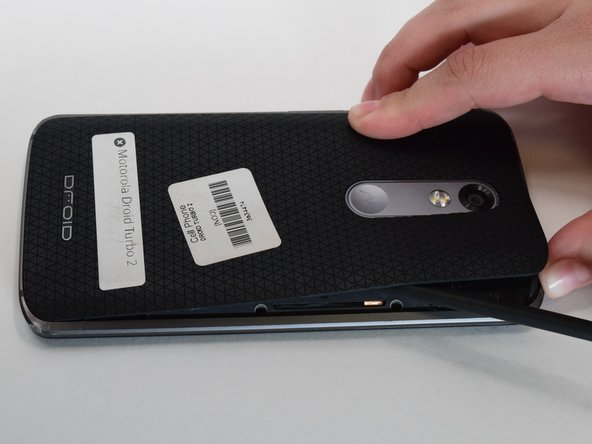 Use an iOpener, heat gun, or hair dryer to heat the back side of the phone in order to soften the adhesive securing the back panel.