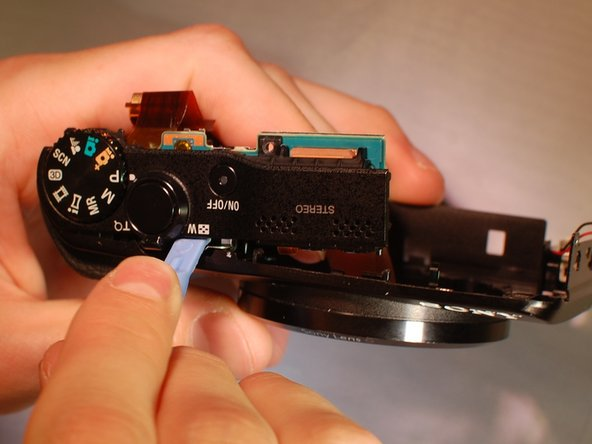 "Using the plastic opening tool between the front edge of the camera and the top ""control assembly"", pry and unhook the claws roughly located in the red square."