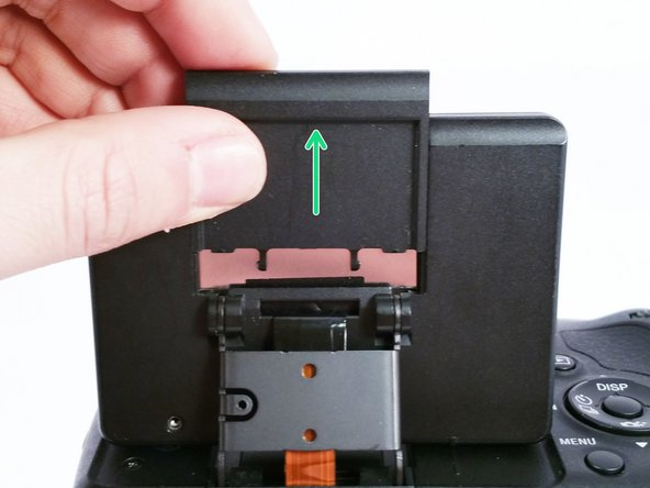 Remove the plastic cover from the back of the LCD display by simply sliding it up and off of the camera.