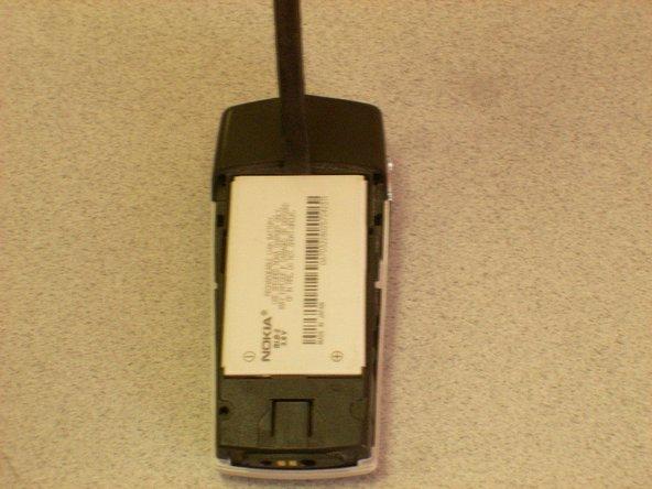 Insérez un tournevis ou un spudger dans l'encart  au-dessus de la batterie.