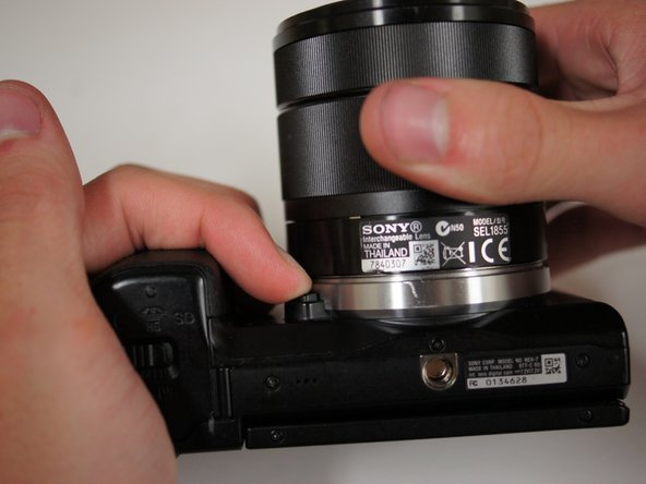 Image 1/2: Press the button located next to silver lens mount and rotate the lens counterclockwise.