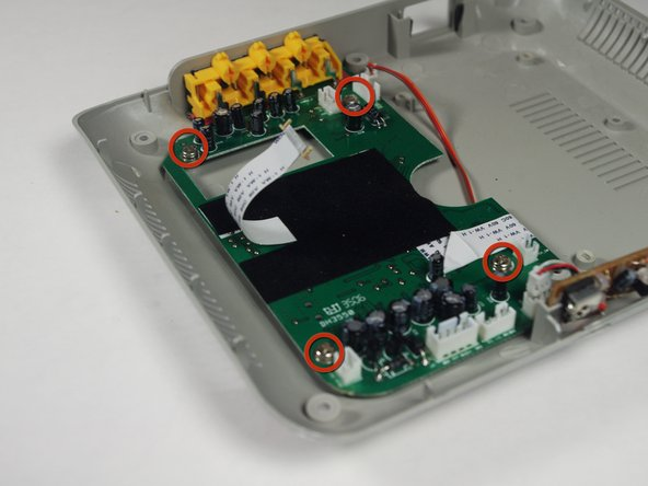 Image 1/3: Place the plastic opening tool underneath the circuit board, and lift up genttly. As you lift up, slide the circuitboard in a direction away from the AVI ports.