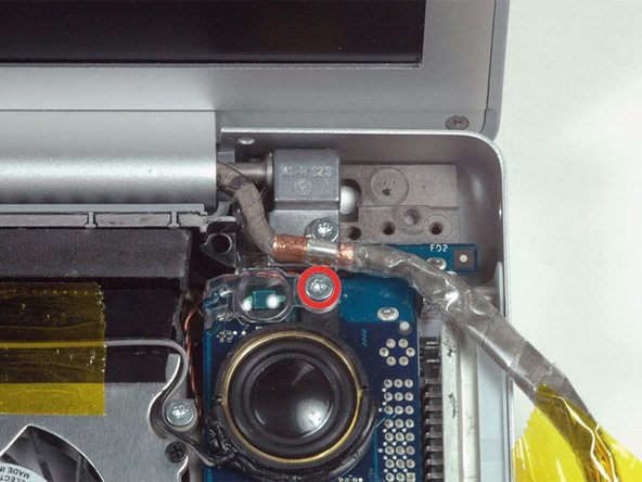 Image 1/1: Remove the silver T6 Torx securing the ground loop in the display data cable to the casing.