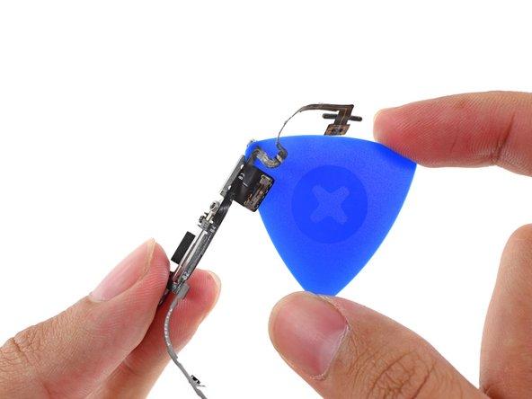 Faites glisser le médiator sous la partie restante du commutateur verrouillage/verrouillage pour le décoller du support du bouton.