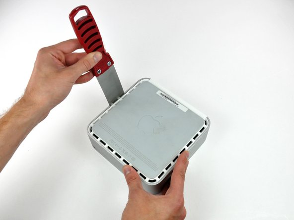 Image 1/3: Gently enlarge the existing crevice by prying the handle of the putty knife downward and away from the mini.