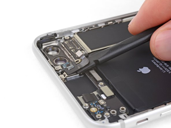 Slide the flat edge of a spudger underneath the antenna flex cable to separate the adhesive holding it in place.