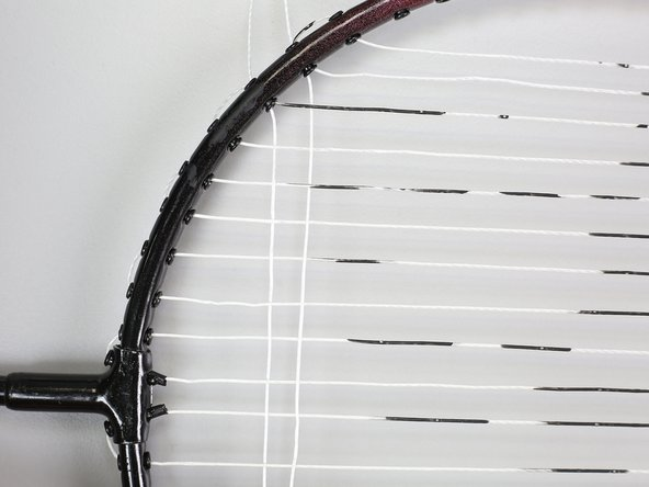 Thread the horizontal strand straight across and through the hole opposite the one you started at. Loop back into the next hole up the side of the racquet.