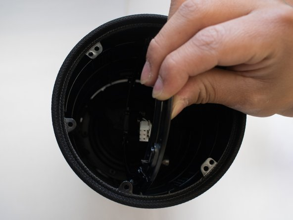 Carefully push the ring attached to the cable through the shell.
