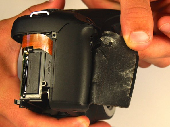 Gently remove the rubber grip by pulling the adhesive side up and away from the camera.