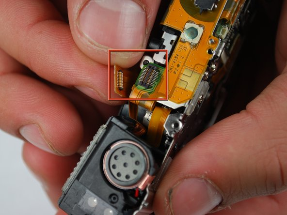 Image 1/1: Begin by disconnecting the hanging flash/speaker unit from the connector on top of the camera.