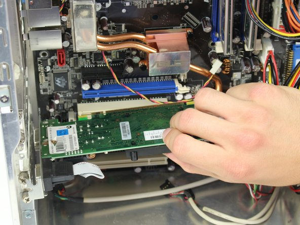 Press the latch on the side of the connector area to unlock the graphics card, and carefully slide the graphics card out from its slot in the computer.