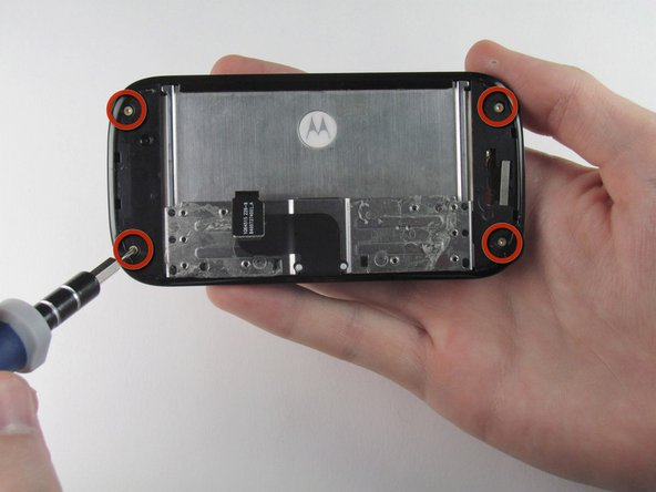 Remove the four 3.0 mm T4 Torx screws at the corners of the phone.