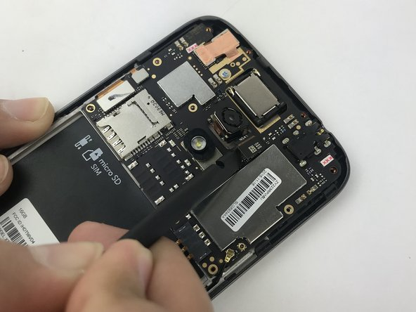 Use the flat end of a spudger to disconnect the rear-facing camera connector from its socket on the mother board.