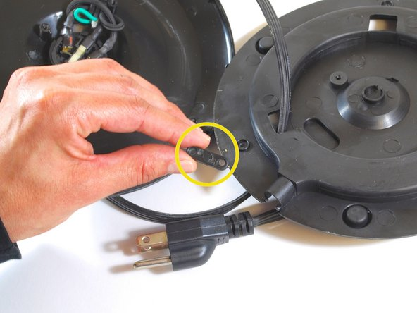 Remove the clamp which holds the cord in place.