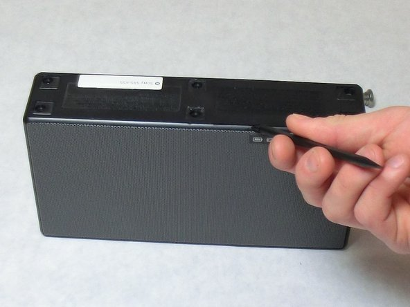 Insert a plastic spudger at the seam of the bottom panel and remove it from the rest of the speaker.