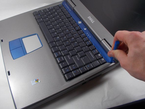 Remove the plastic face plate from the laptop using the iFixit Plastic Opening Tool.