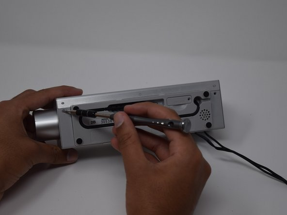 Remove the screw from the backside cover of the Sony Dream Machine with a Phillips Screwdriver.