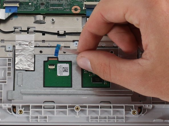 Gently remove the adhesive on the touch pad ribbon cable.