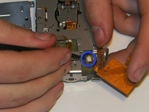 Image 2/3: The speaker will still be connected to the board via two small power wires. Use the tweezers to pull and unplug the power connector from the main rear accessory board.