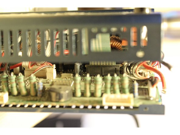 The top cover is still connected by three ribbon cables to the mainboard. Gently lift the top cover until you can slide your fingers or a spudger into the charger to disconnect the three molex connectors.