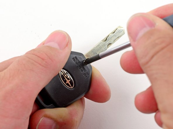 Unscrew the single Phillips screw on the back of the key fob using a #1 Phillips screwdriver.