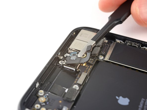 The screw boss at the top of the antenna flex cable is tucked into a small recess in the top edge of the iPhone.