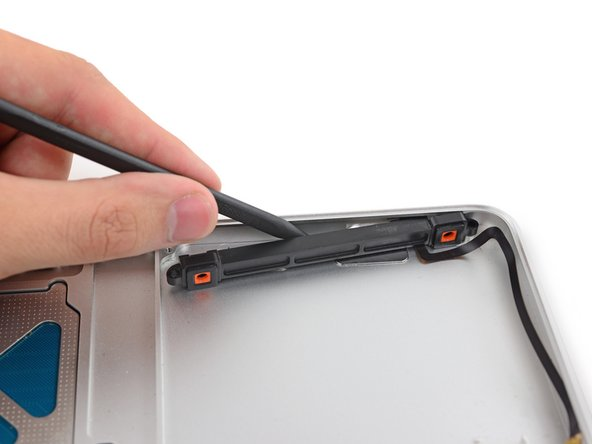 Insert the tip of the spudger between the hard drive bracket and the front edge of the upper case to free it from its recess.