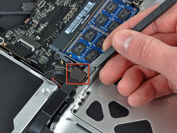 Use the flat end of a spudger to pry the hard drive/IR sensor cable connector up off the logic board.