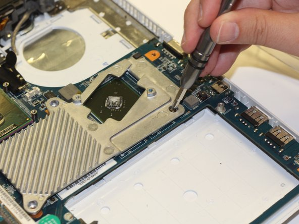 Next, using your fingers, lift up on this metal piece and remove it from the motherboard.