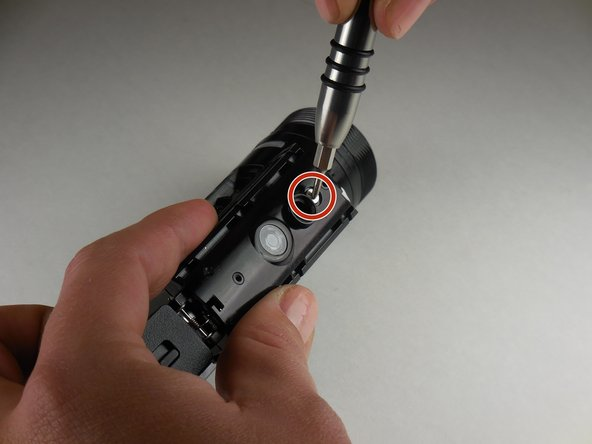 With a phillips head screwdriver (PH 000), remove the 5.54 mm (0.218 in) screw located next to the tripod screw-in.