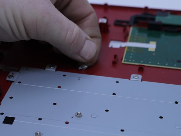 Peel the silver tape off of the keyboard back plate.