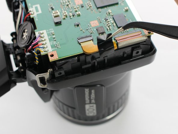 Gently tilt the  the lock for the ZIF cable attached to the motherboard with a plastic removal tool.