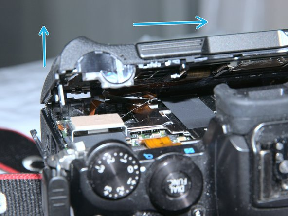 Gently, lift (towards back) and slide the back cover towards left (THE LEFT when you holding the camera)