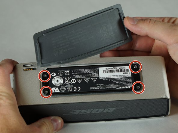 Peel back the rubber battery cover and remove the four circled 6.0 mm screws using a T8 Torx Screwdriver.