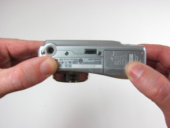 Image 2/3: The battery cover will spring open, so be careful to lift it up gently.