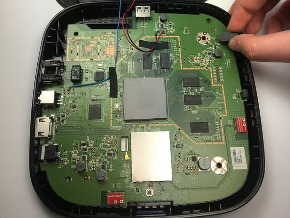 To begin removing the motherboard from the plastic casing, pinch the black plastic clip and gently pull upward.