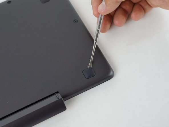 Image 2/3: Use the metal spudger to remove the rubber feet nearest to the top of the keyboard, where the connecting dock to the screen is. There are two 6mm screws under these rubber feet.
