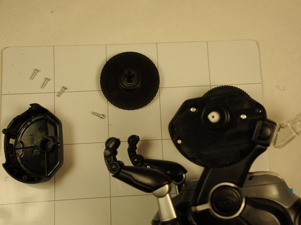 Remove 1.2 mm Phillips screw from the white plastic piece in the center of the wheel and then remove the wheel entirely.