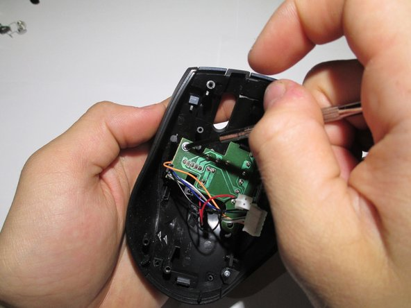 Take the upper housing of the mouse and begin to remove the two screws (highlighted in red) that hold the board in place.