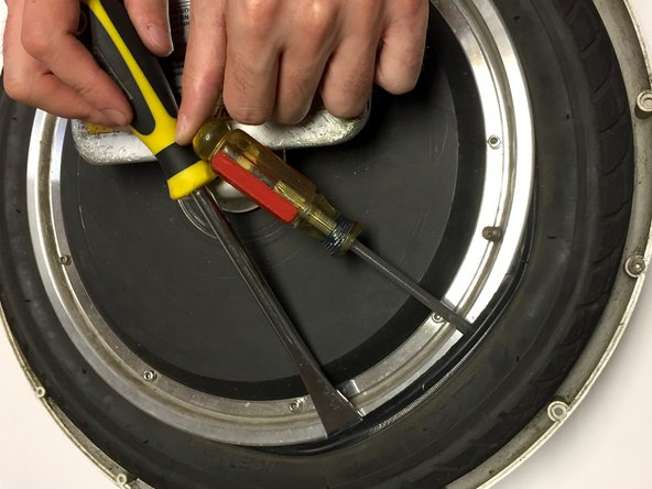 Once inserted, tilt the tool back toward the middle of the wheel to loosen the rubber tire from the metal rim. The edge of the rubber tire should now be above the metal rim.