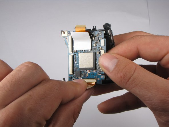 Image 1/3: Carefully remove the large ribbon-wire by pulling the wire where it connects with the motherboard.